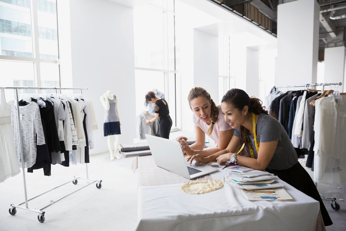Two female fashion retail store employees working inside a store
