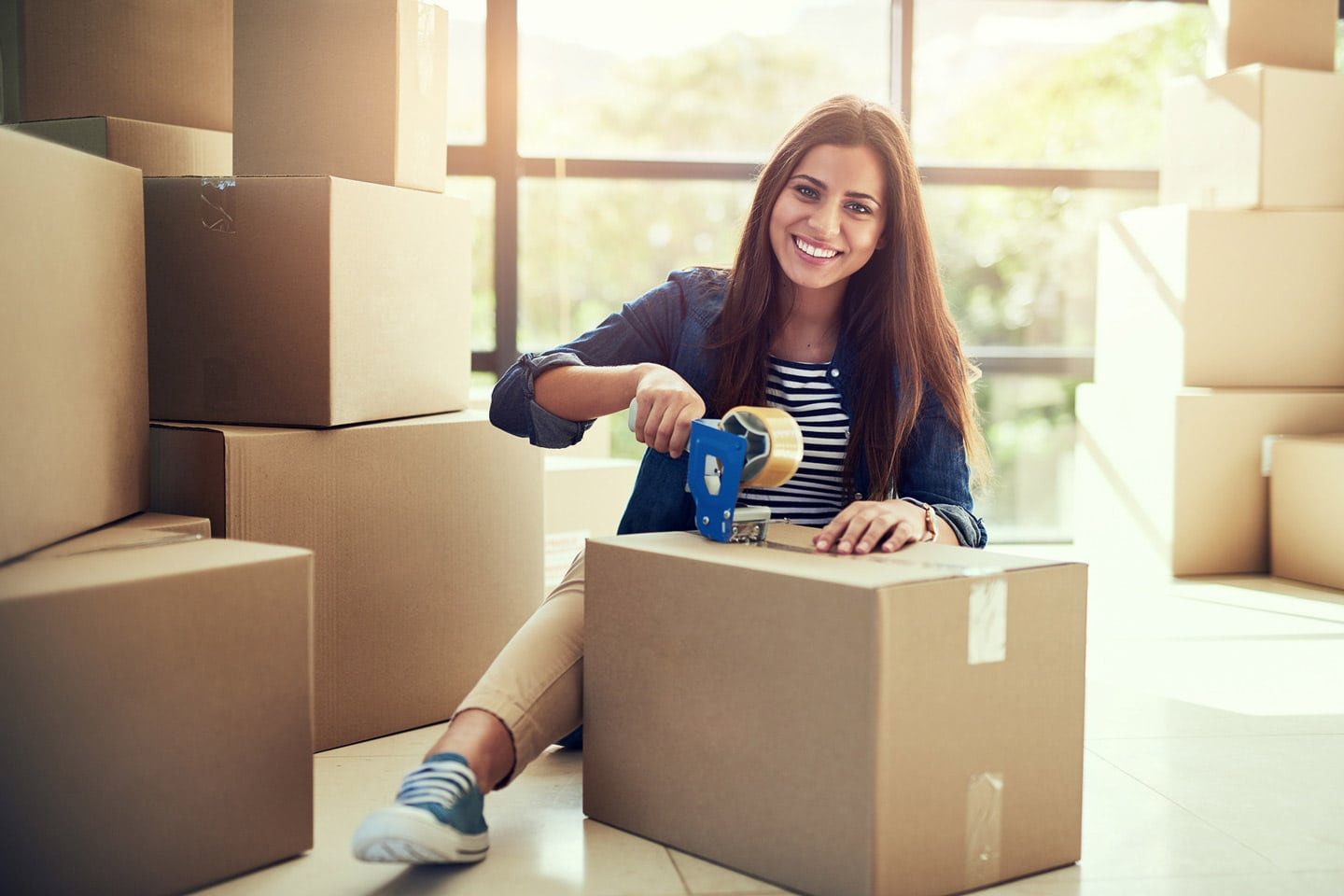 Woman packing boxes for a business relocation move
