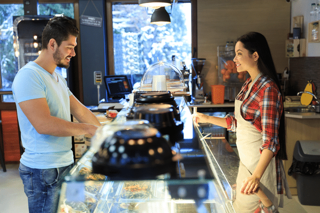 A person ordering food at a fast casual restaurant counter