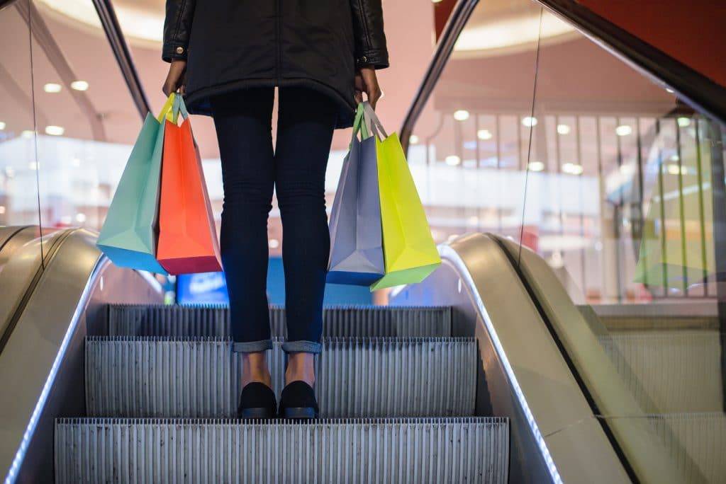 Woman holding bags on a shopping mall escalator