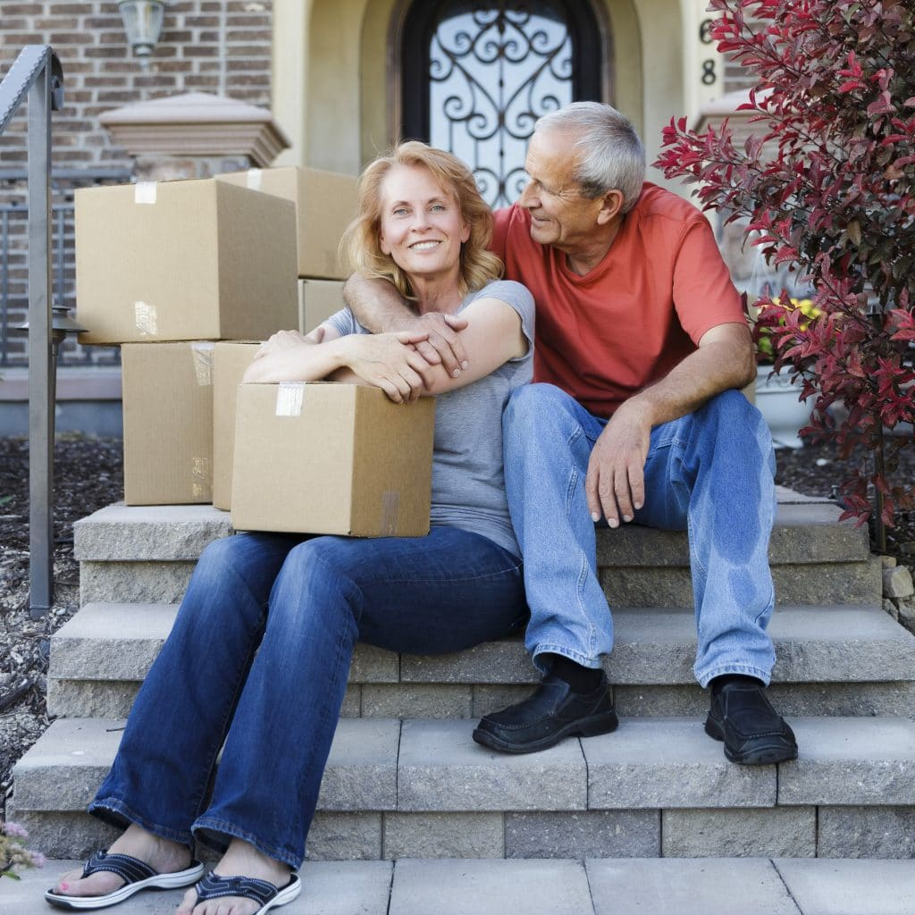 A relocating couple sitting on the steps of their home