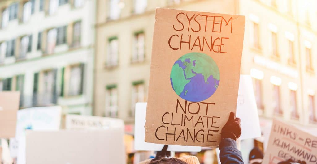 A sign about climate change sign being held at a protest.