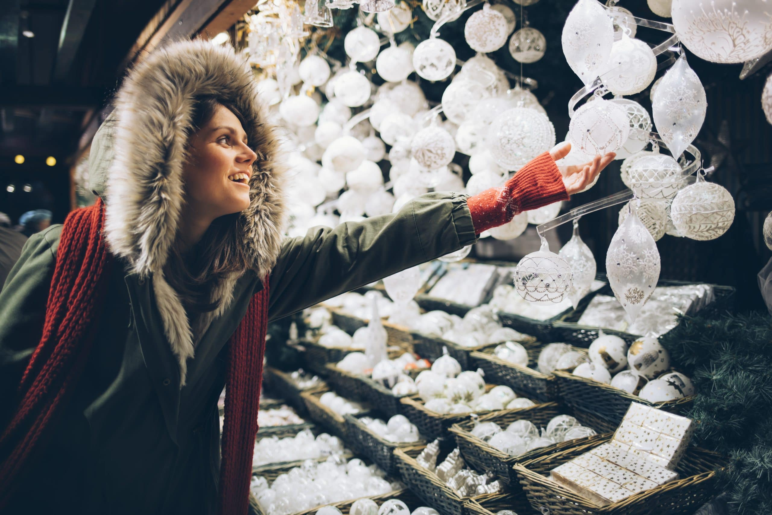 A woman browsing Christmas ornaments at a seasonal pop-up shop.