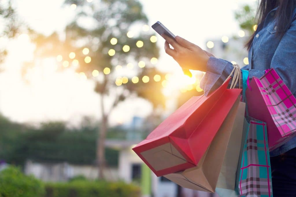 Woman holding a smartphone and shopping bags at an outdoor retail area