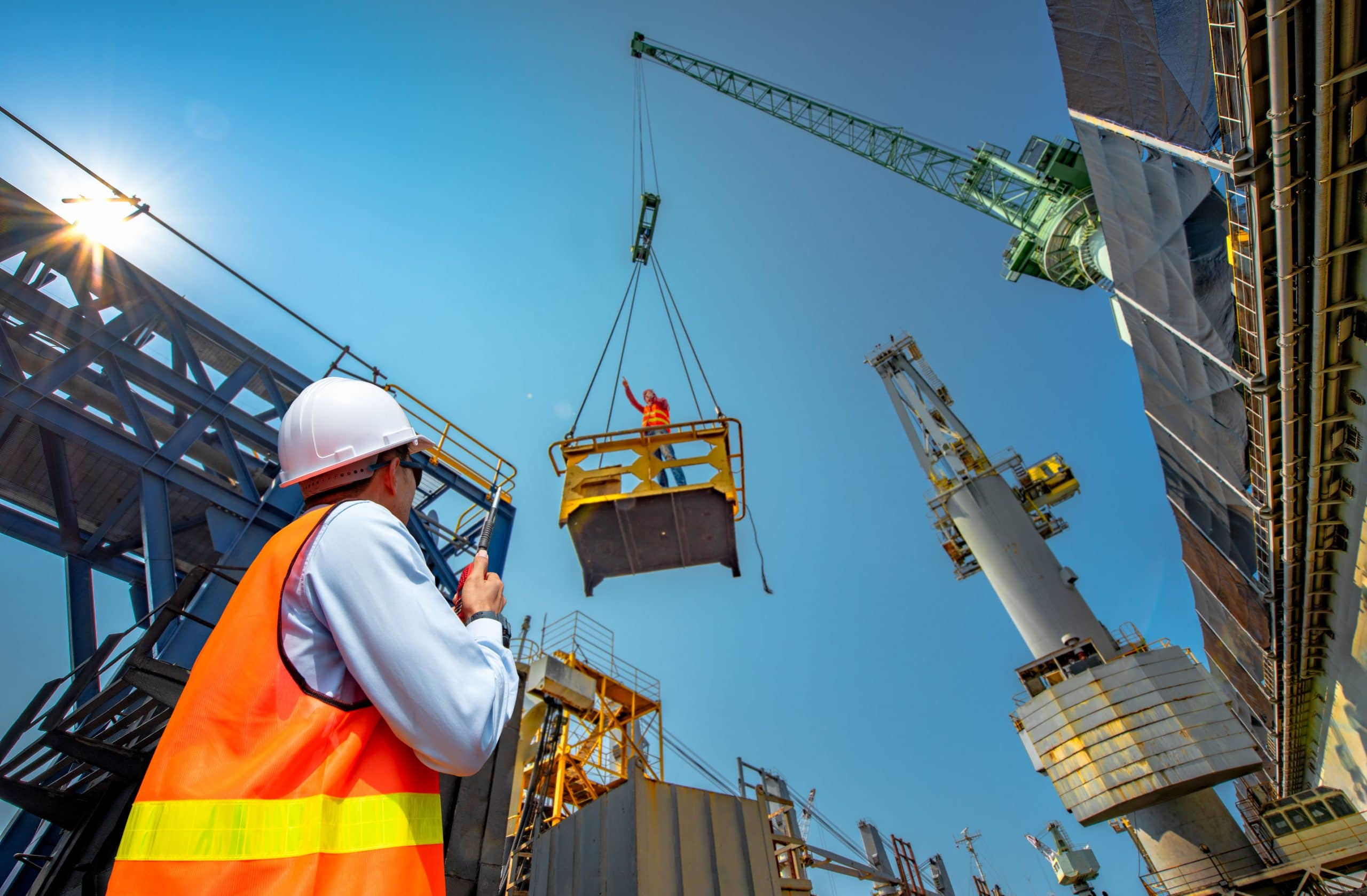 Construction project supervisor watching works on crane lifts