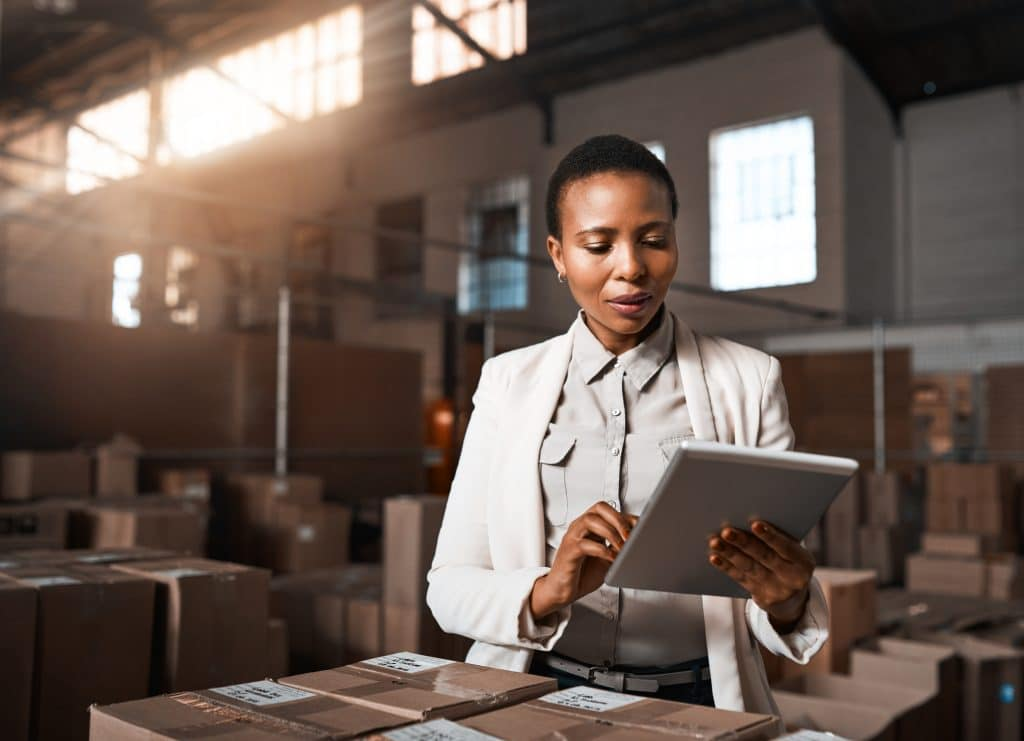 Female employee in a packing warehouse using a tablet to keep track of supply chain data