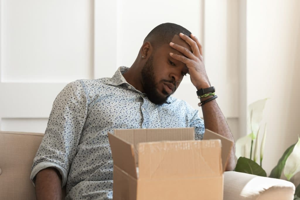 Man inside home unhappy looking at the contents within his opened delivery box