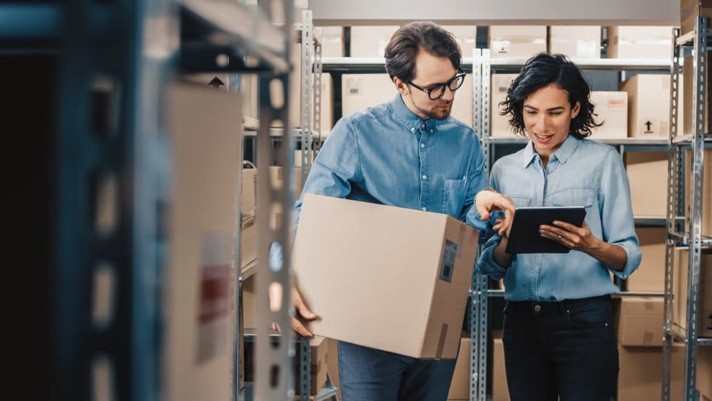 Two employees reviewing inventory on a tablet in a stockroom