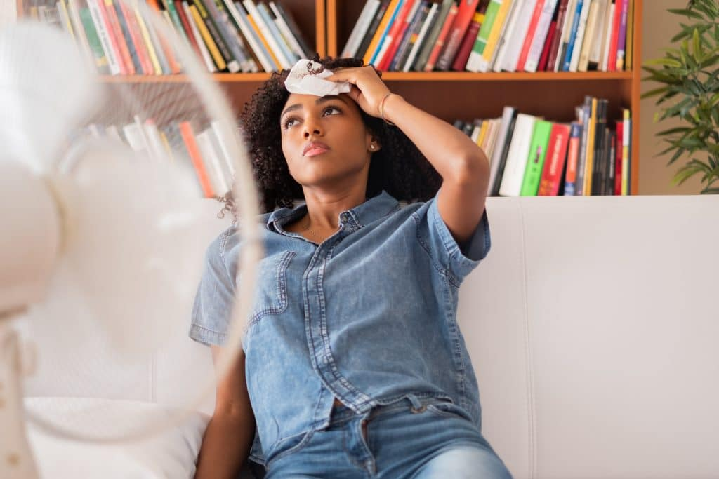 Woman sitting on her couch while wiping sweat off her forehead