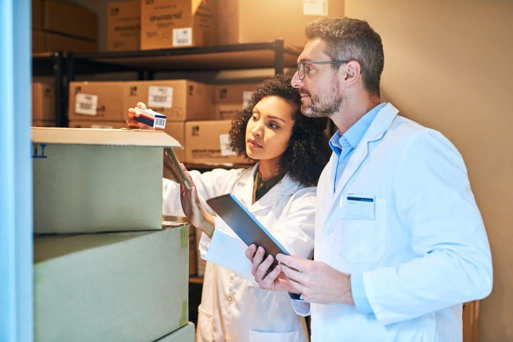 Two medical hospital supply chain professionals  looking at boxes in a warehouse