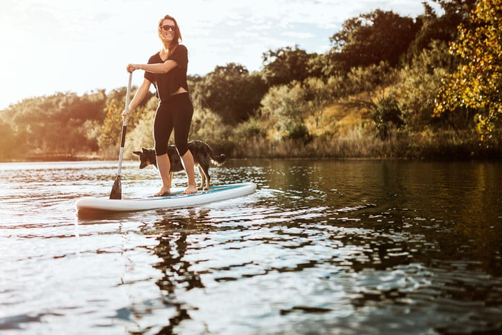 A woman paddle-boarding on a river in Austin, Texas