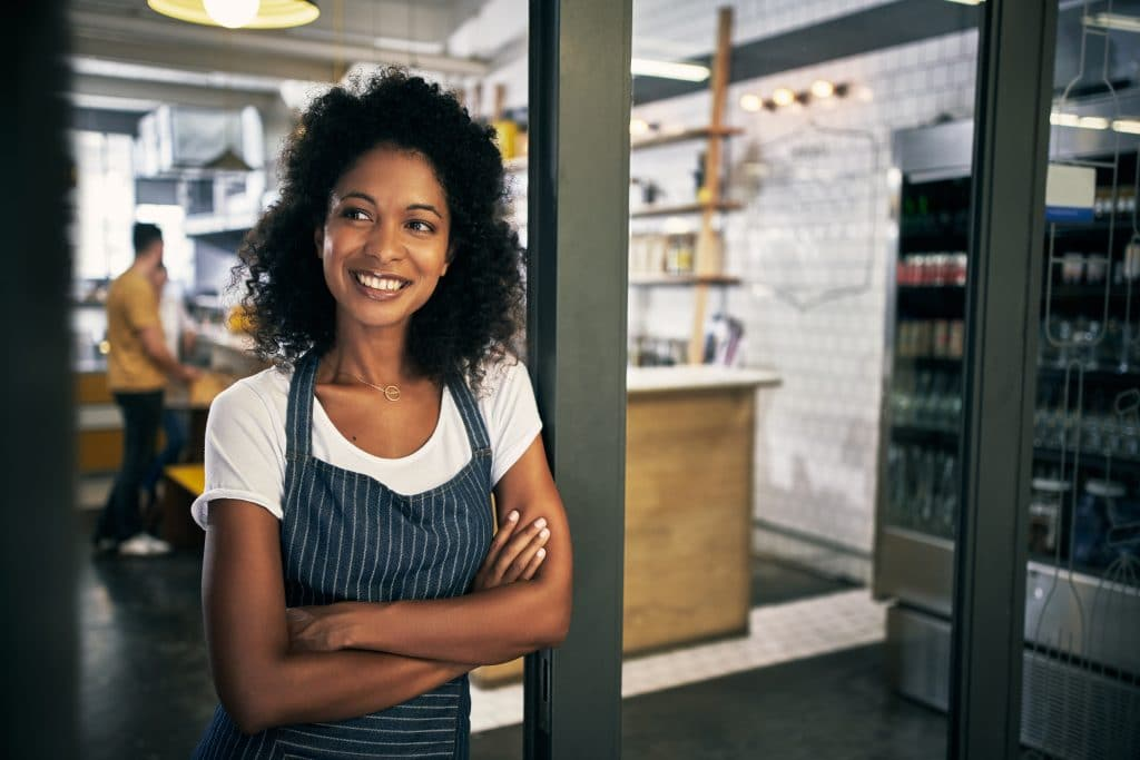 Smiling business owner standing inside franchised food service business