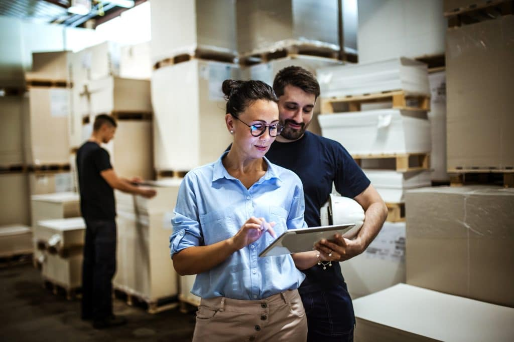 Warehouse employees reviewing inventory for supply chain managemnt