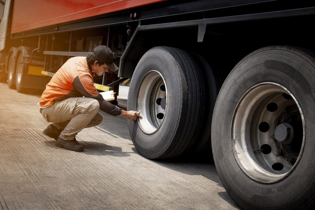 A trucker checking the tires on a semi truck