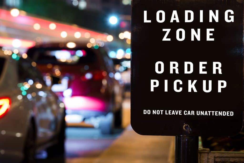 Cars in line at night at a curbside pickup area with sign