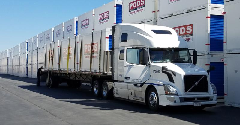 A parked semi truck loaded with three PODS containers