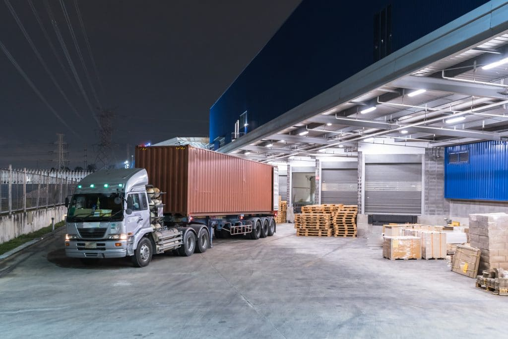 A freight truck loaded with a shipping container pulling out of a loading dock