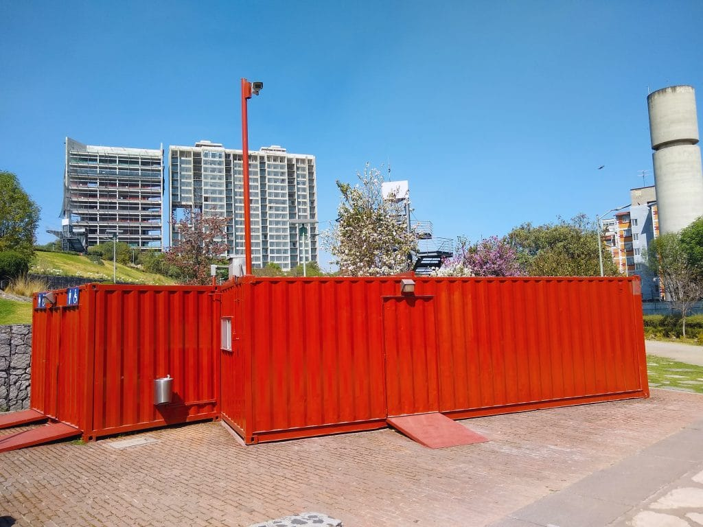Two large red shipping containers sitting on the ground at a park