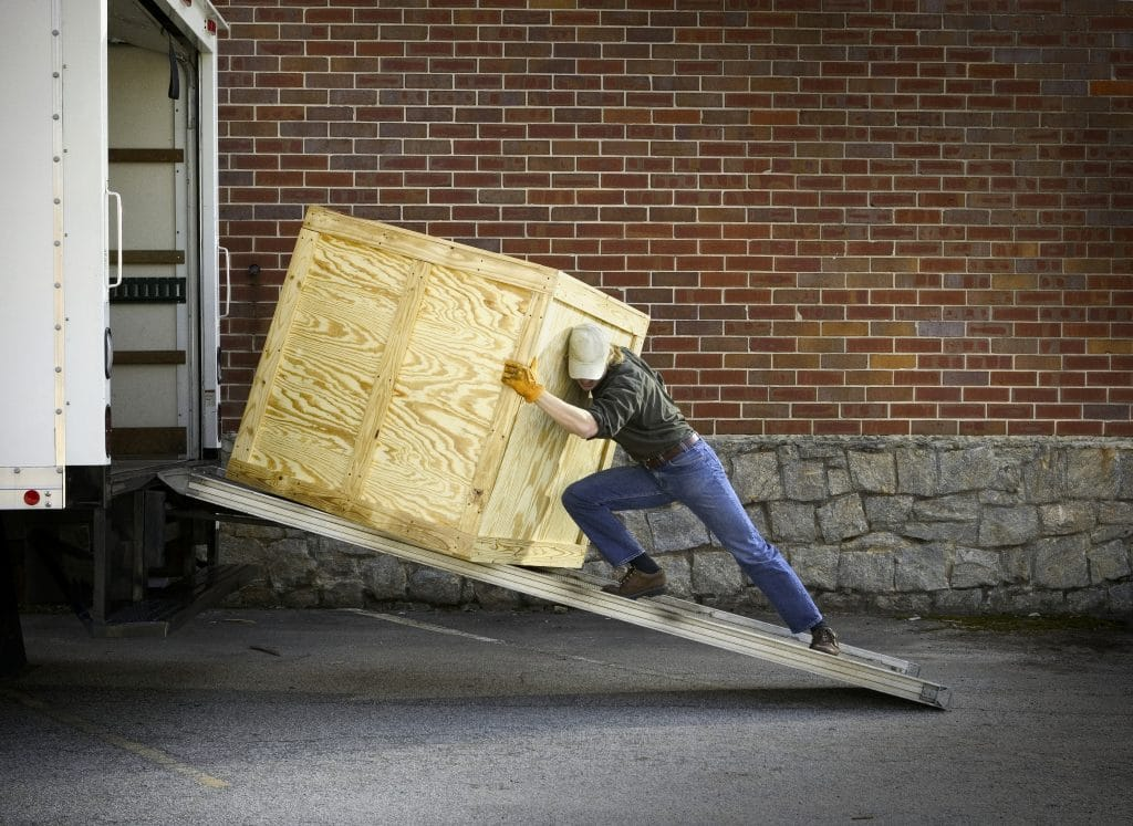 A man pushing a wood crate on a ramp into a truck