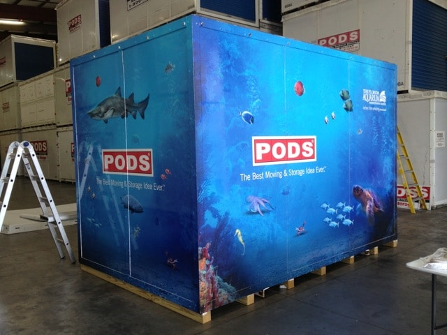 A modified shipping container with a custom aquatic decal wrap