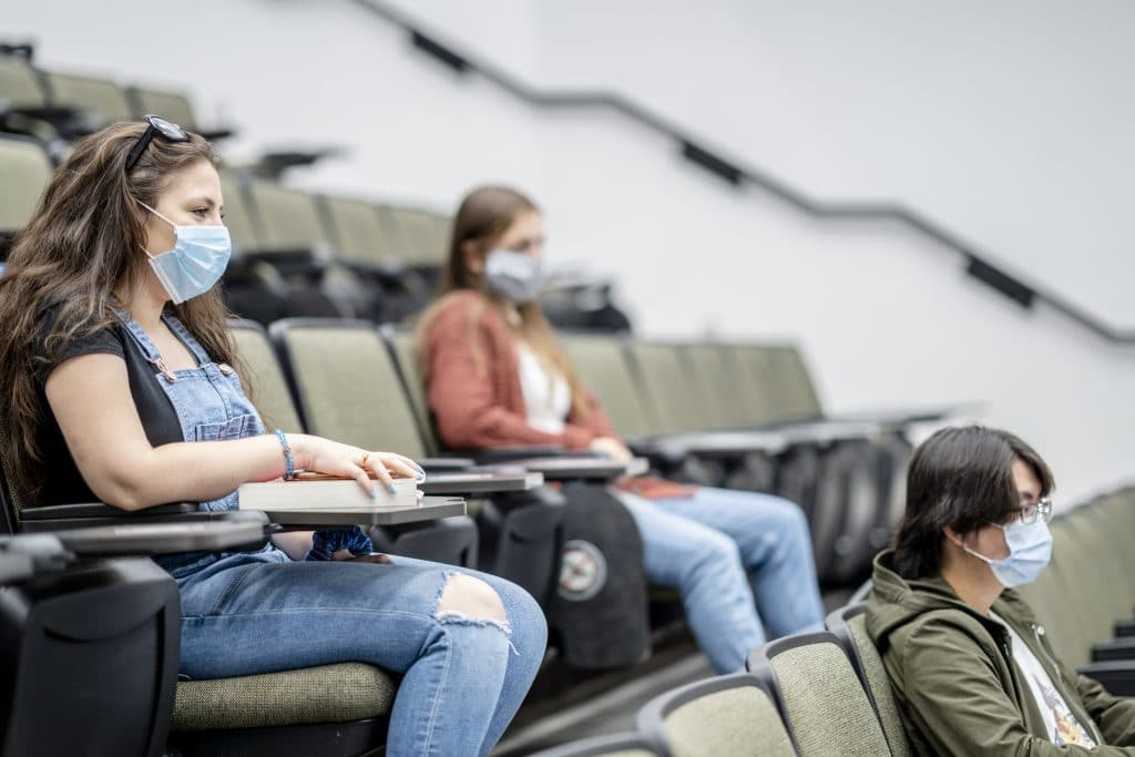 Students wearing masks and sitting socially distanced in a lecture hall