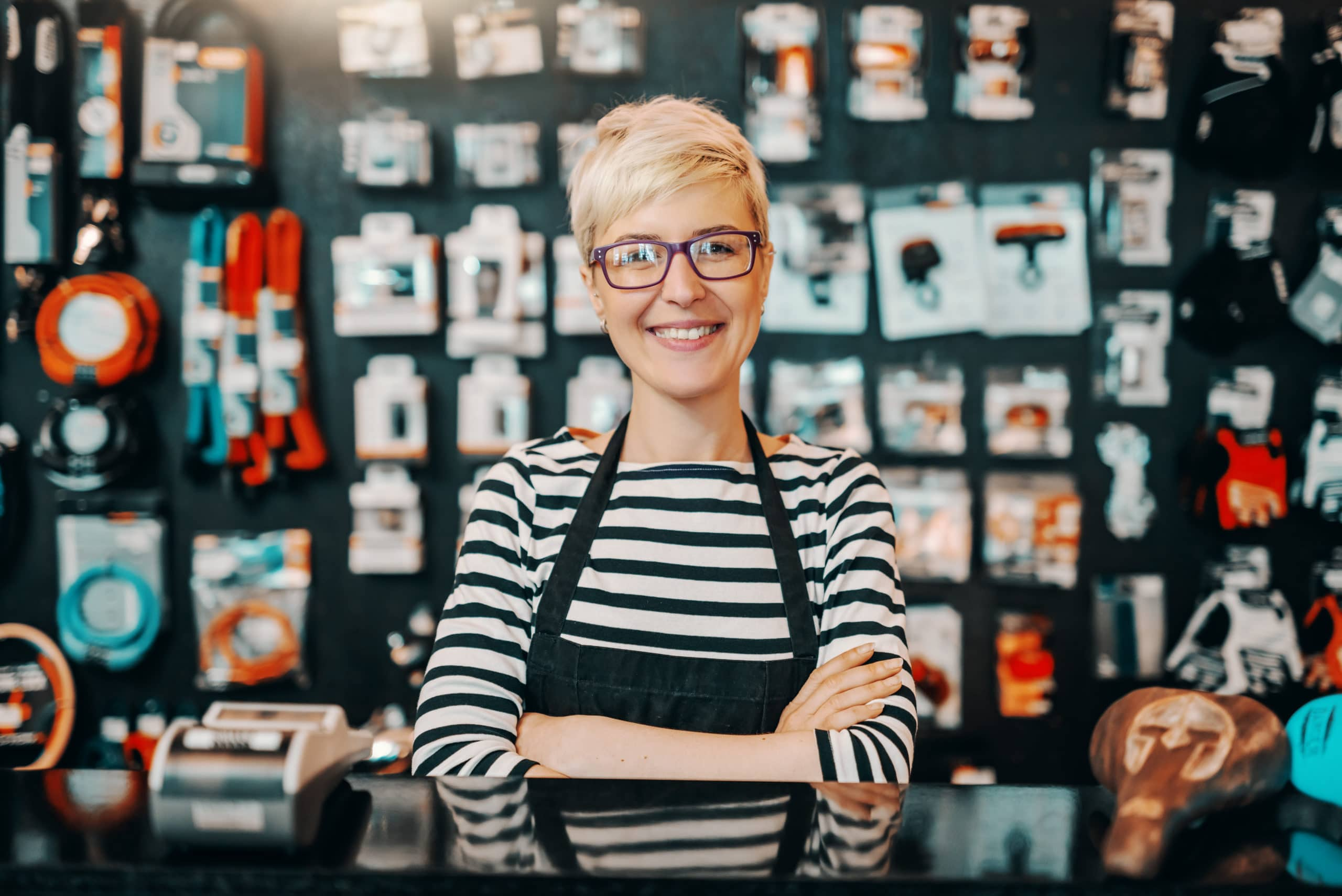 Portrait of a smiling Caucasian female worker with short blonde hair standing in bicycle shop with arms crossed.