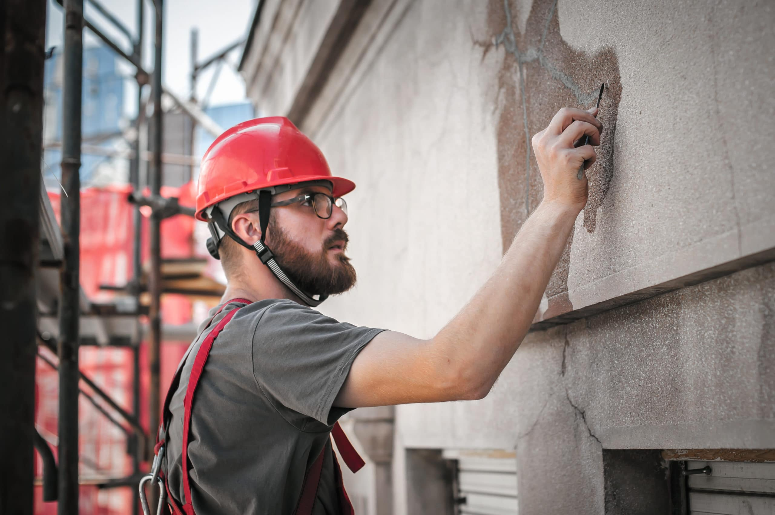 Restoration professional standing on a scaffold and repairing the exterior of a building