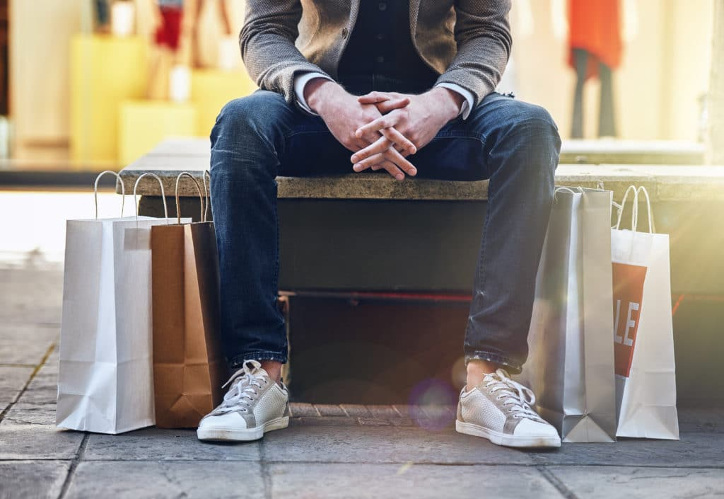 Shot of a man sitting on an outdoor bench with his shopping bags on the floor